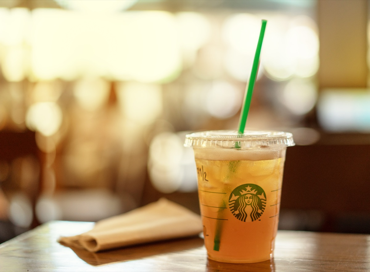 BANGKOK, THAILAND - JUNE 22,2018 : Starbucks iced lemon tea on a wooden table in Starbucks coffee shop with brown napkin paper.