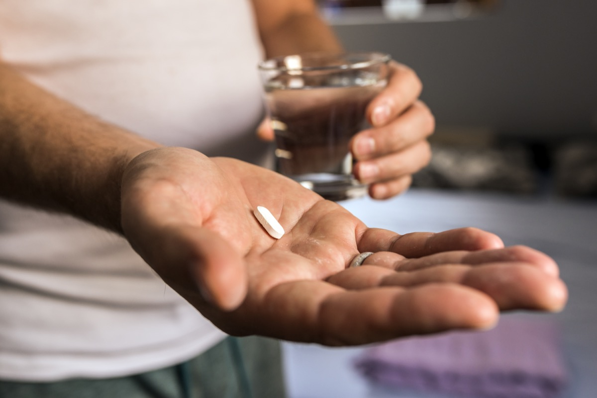 age, medicine, healthcare and people concept - close up of mature man hands with white pill and water glass at home. Health care and medical concept. Male taking medication, feeling ill. he is going to take some medicine