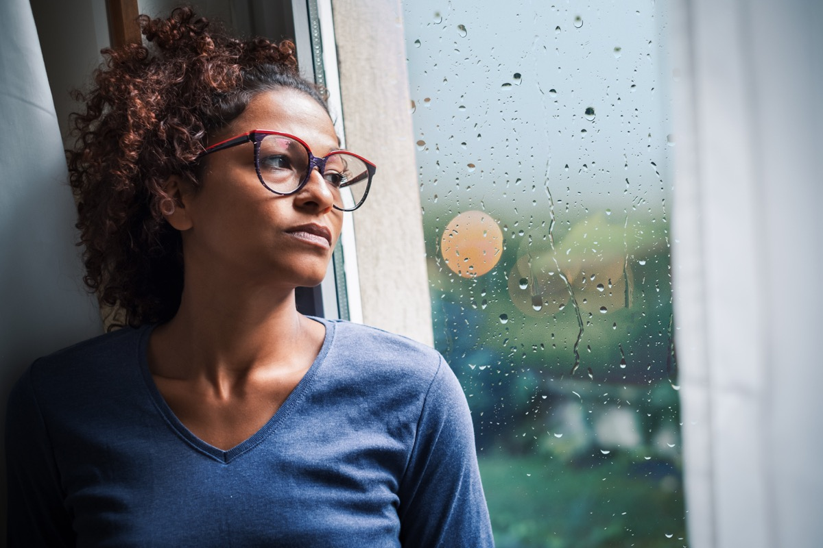 Woman looking out window during a storm