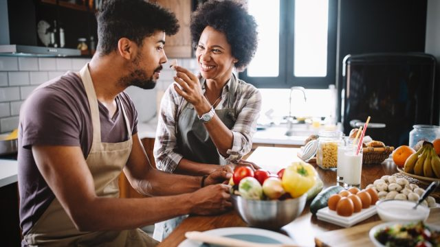 Beautiful young couple having fun and laughing while cooking in kitchen at home