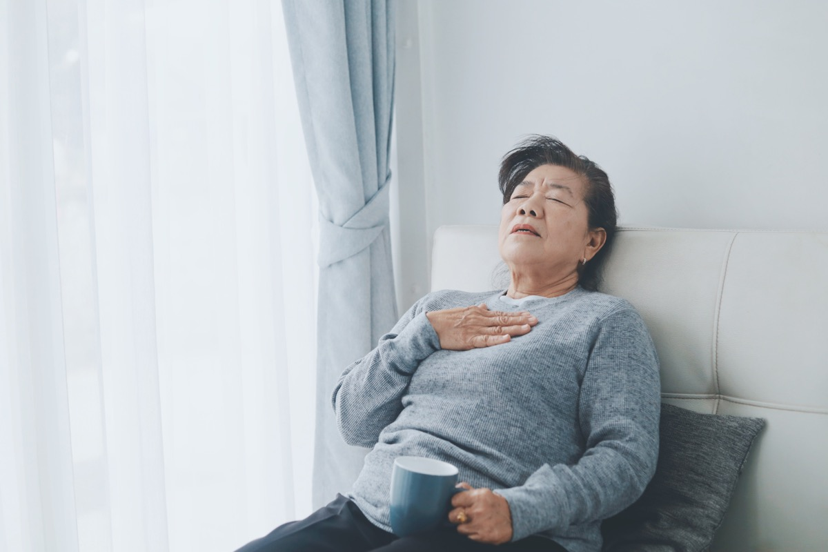 older woman sitting down and having breathing trouble