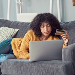 Shot of a young woman using a laptop and credit card on the sofa at home