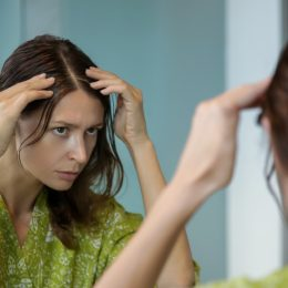 A young woman checking her hair in the mirror for gray strands