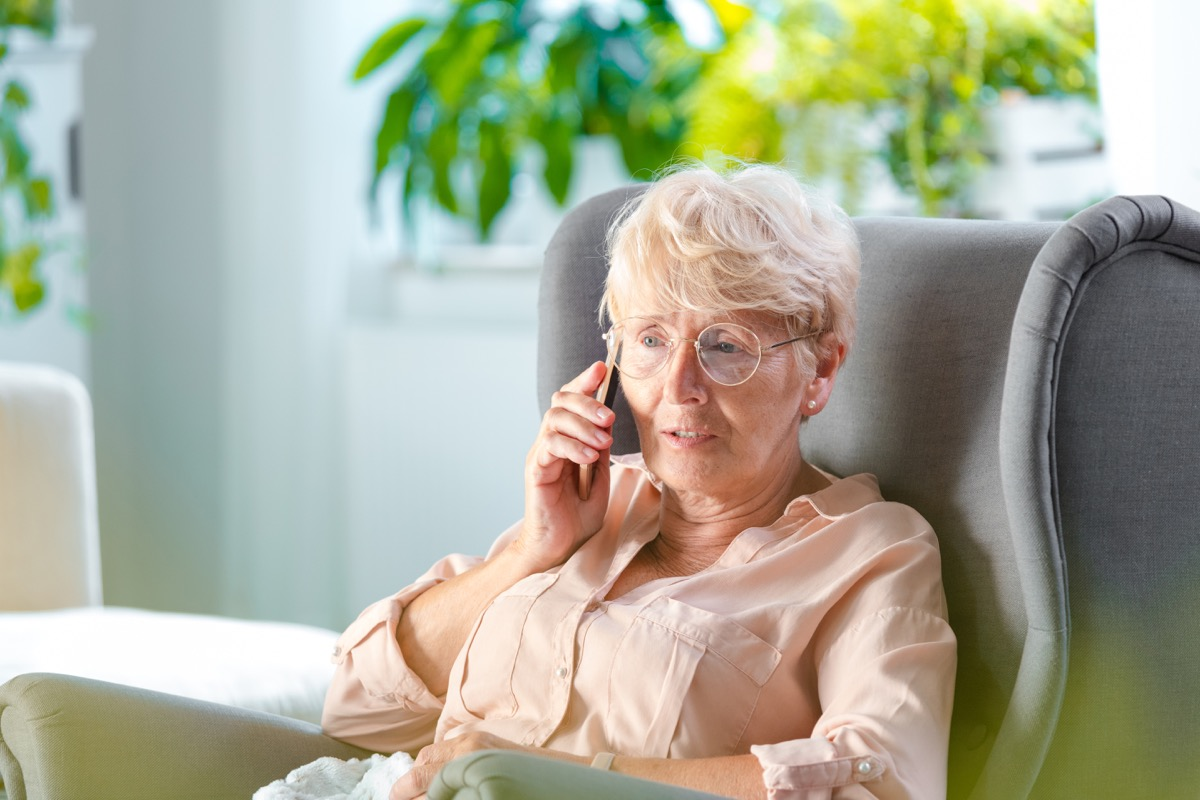 Shot of a senior woman talking on mobile phone while sitting in her room
