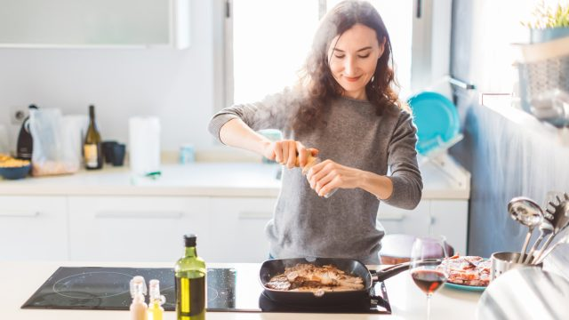 A woman adding spices to a dish while cooking