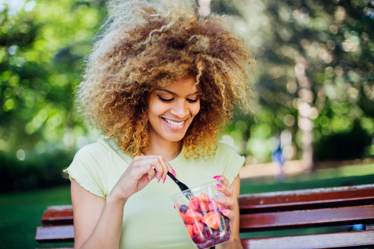 girl sitting at the park, eating fruits and enjoying.
