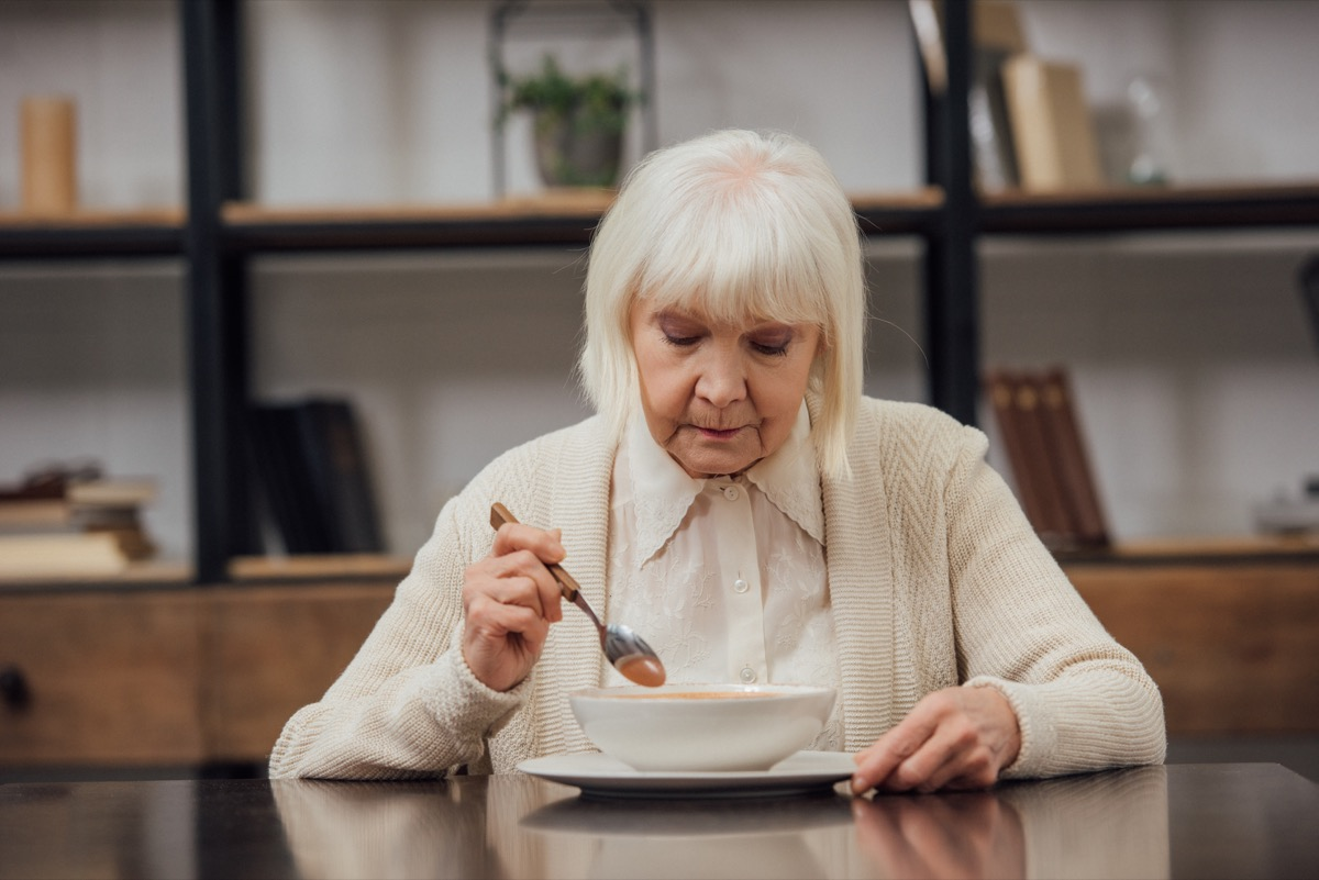 sad lonely senior woman sitting at table and eating at home