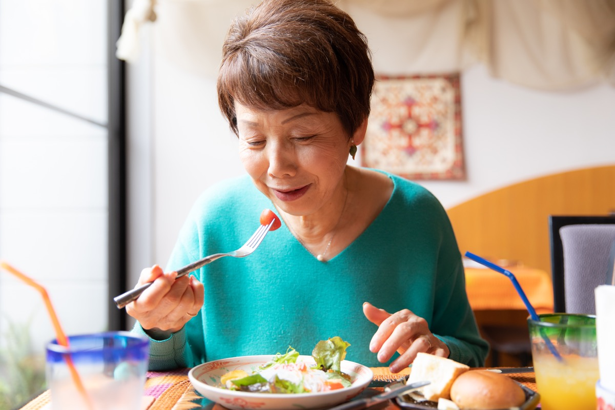 woman eating healthy food with tomatoes in salad