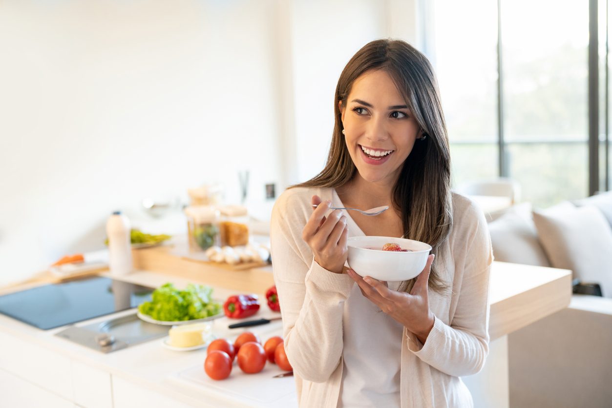 A young woman eating a bowl of yogurt in the kicthen