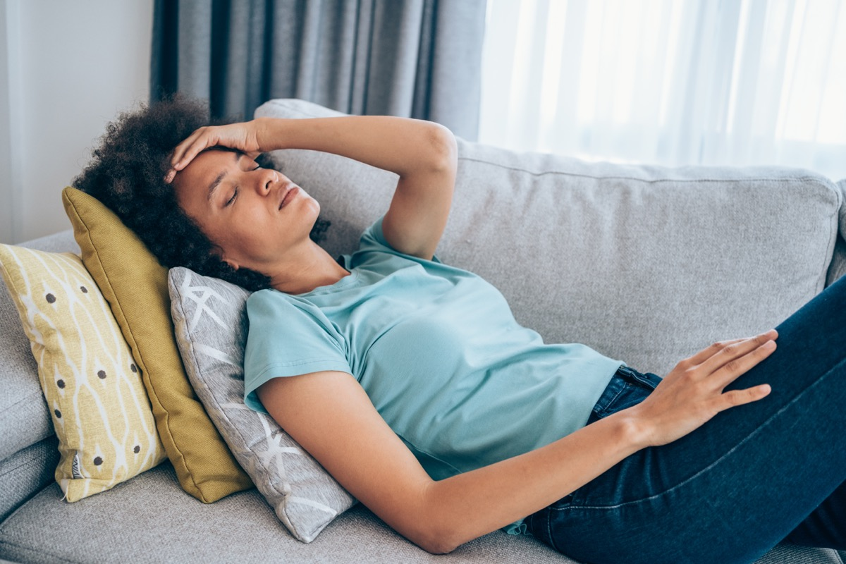 Sick young woman lying on the couch and holding her head with hand. Ill woman lying on the sofa with high temperature.