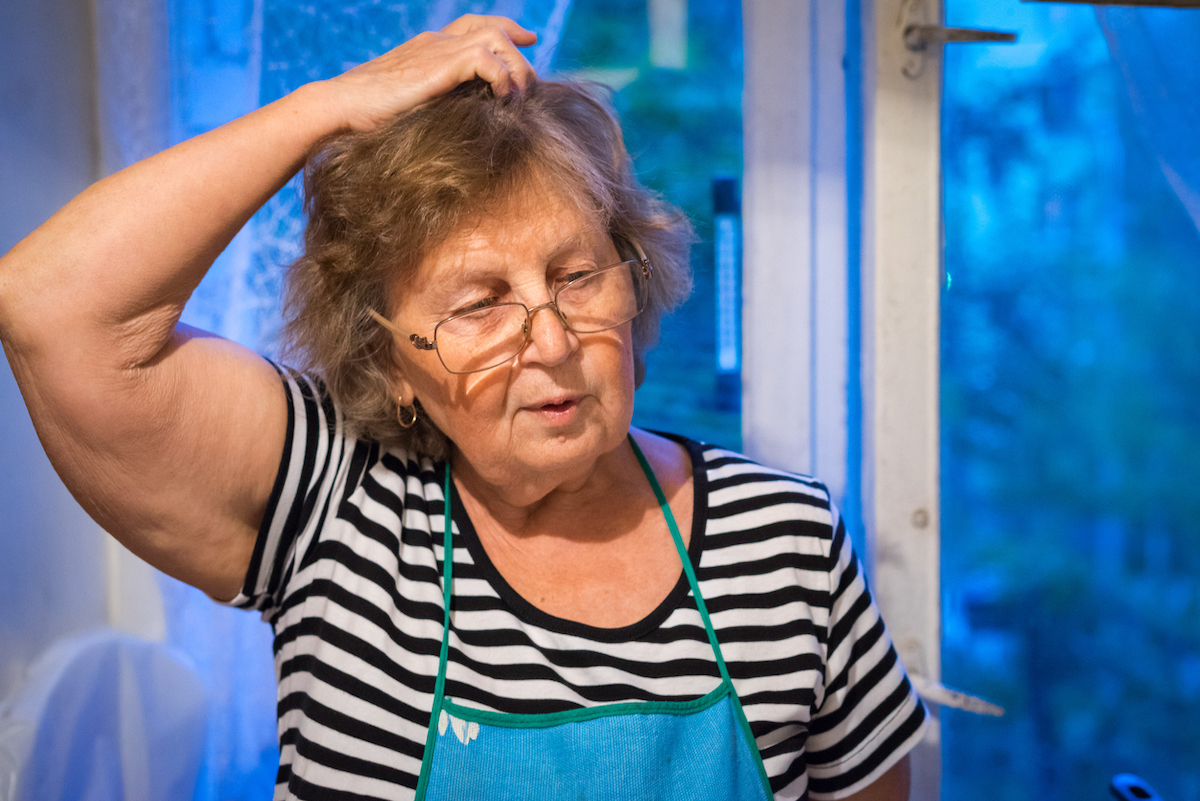 Woman holding hand in hair and looking away while standing against the window with apron on