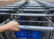 woman holding handle of walmart cart