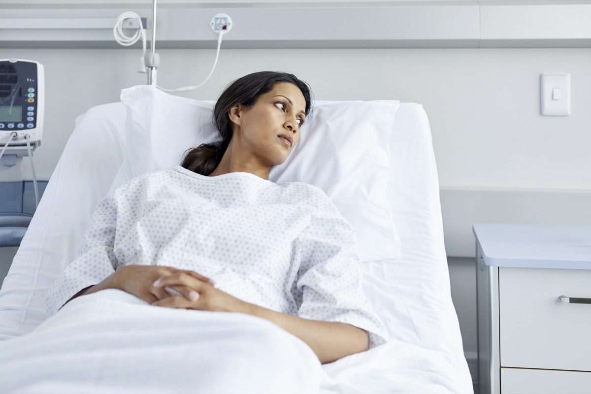Thoughtful patient lying on bed. Female is wearing hospital gown. She is looking away.