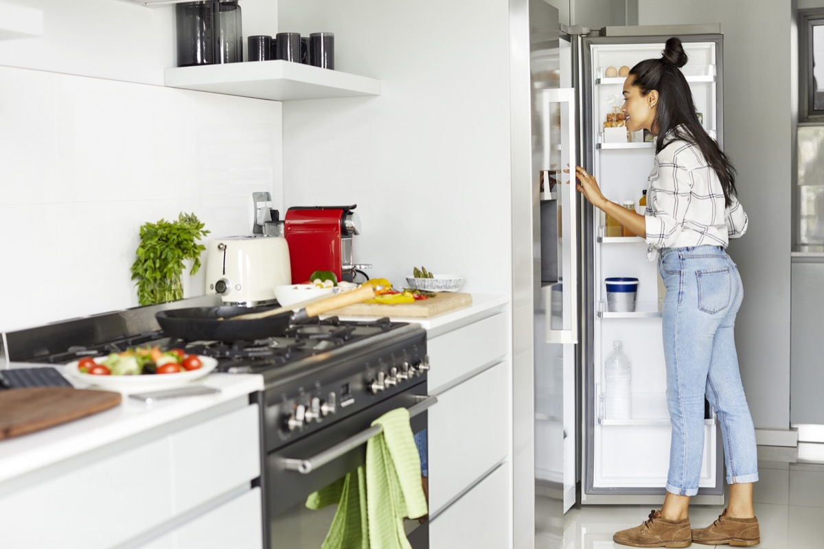 Full length of woman looking into refrigerator. Young female is searching food in fridge. She is standing in kitchen while preparing for meal at home.