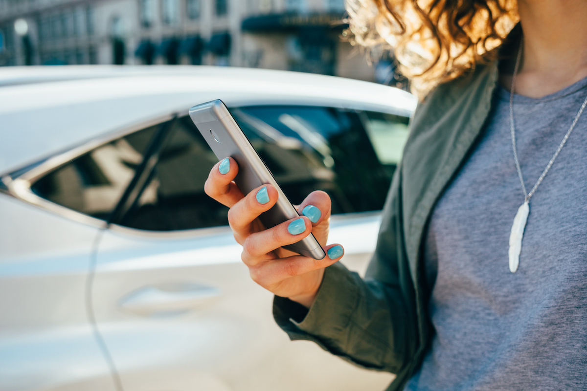 Woman using smart phone standing on street near road and car.