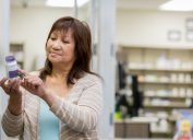 A senior woman reading a vitamin bottle label in the pharmacy