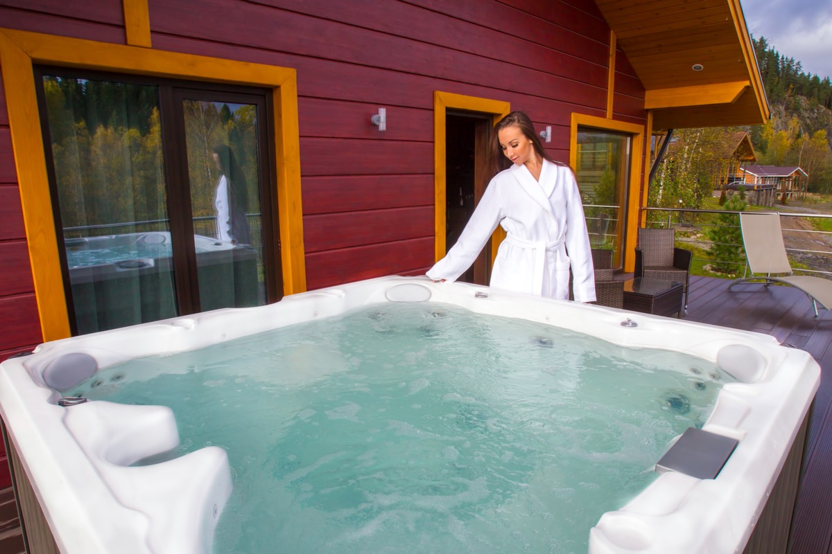woman in white robe standing near hot tub