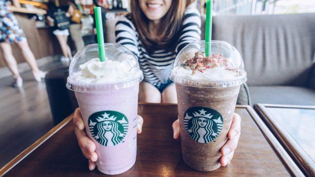 A woman handing over two Starbucks coffee drinks