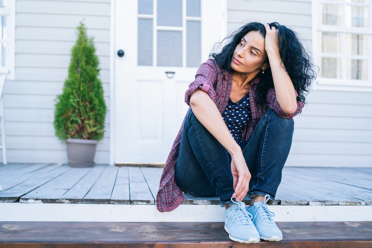 Sad mid adult woman sitting on stairs in front of her house