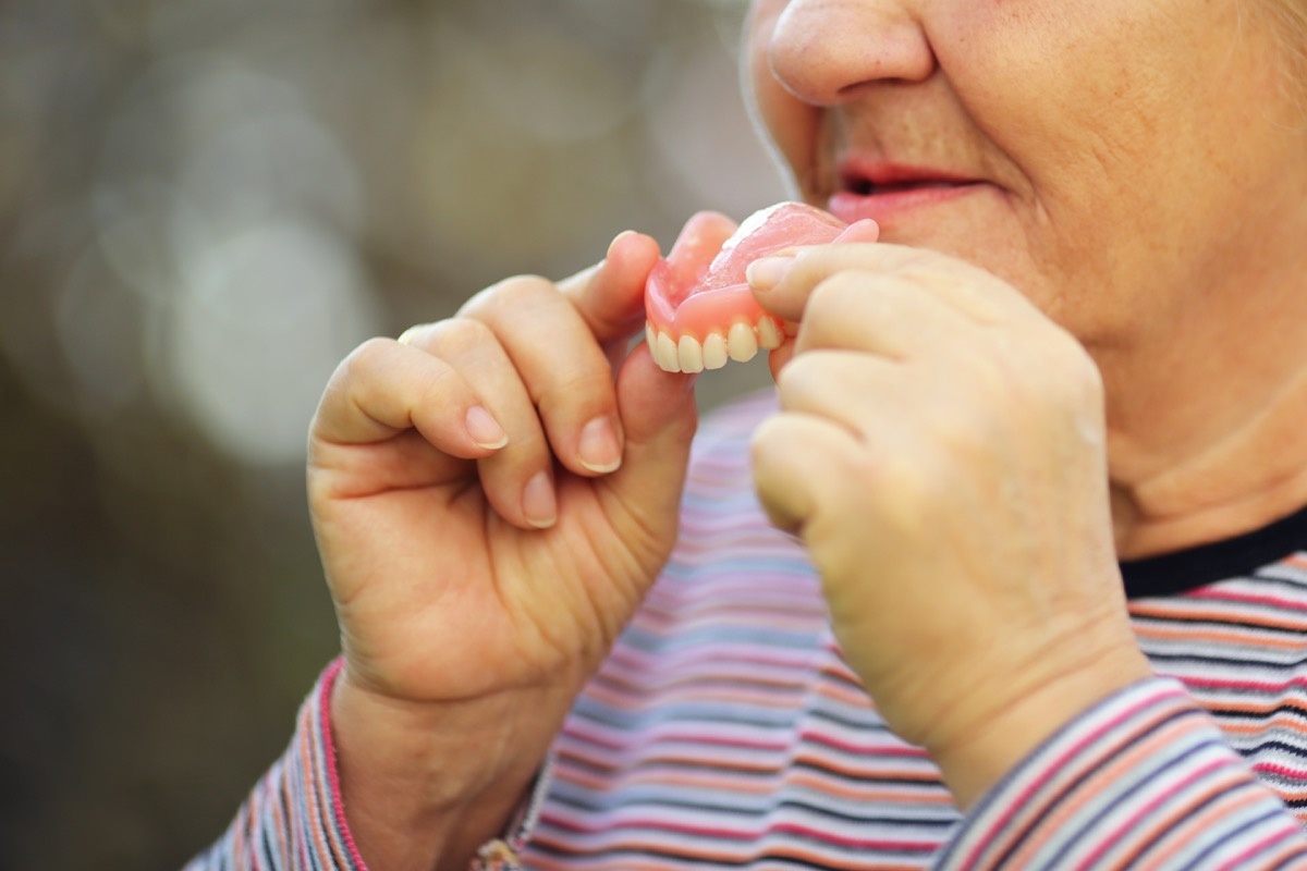 Senior woman taking the teeth out