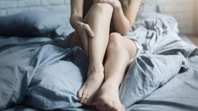 Female legs in bed, closeup. Woman body and skin care, tired legs after working day or fitness workout