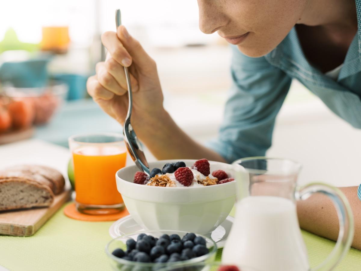 woman eating yogurt with berries