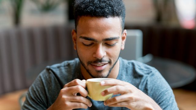 A young man drinking a cup of coffee in a cafe