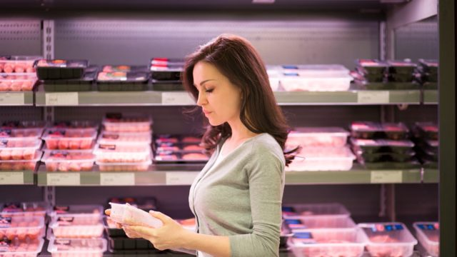 young woman buying meat at supermarket