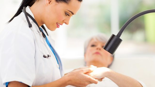 Doctor looking at woman's hands under light
