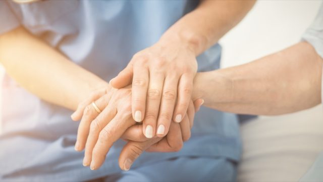Doctor or nurse holding hands with patient