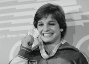 Mary Lou Retton holding up Olympic gold meal in 1984
