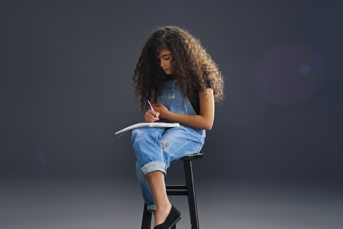Monroe Cannon writing in a notebook while modeling for OshKosh