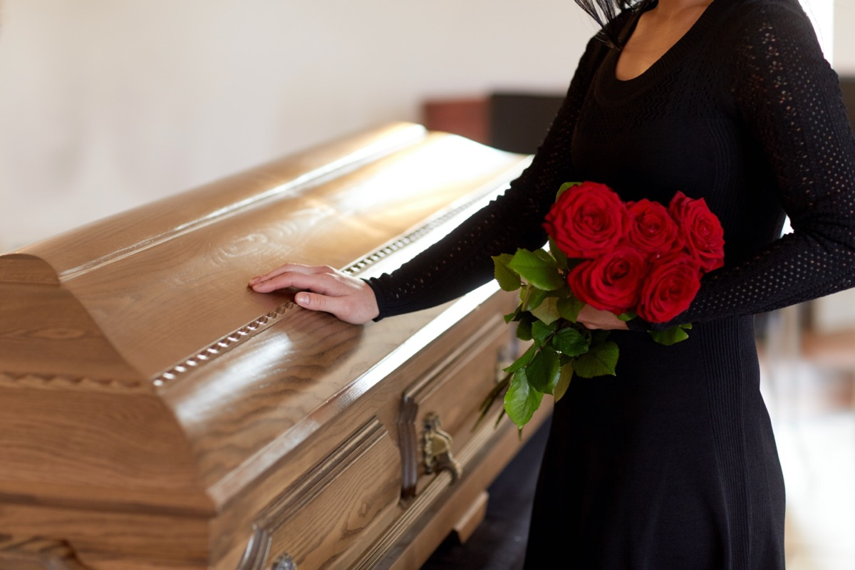 Woman at coffin with roses
