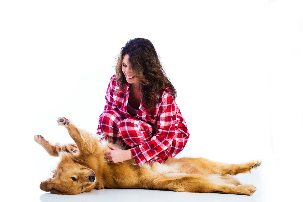 Woman rubbing dog's belly
