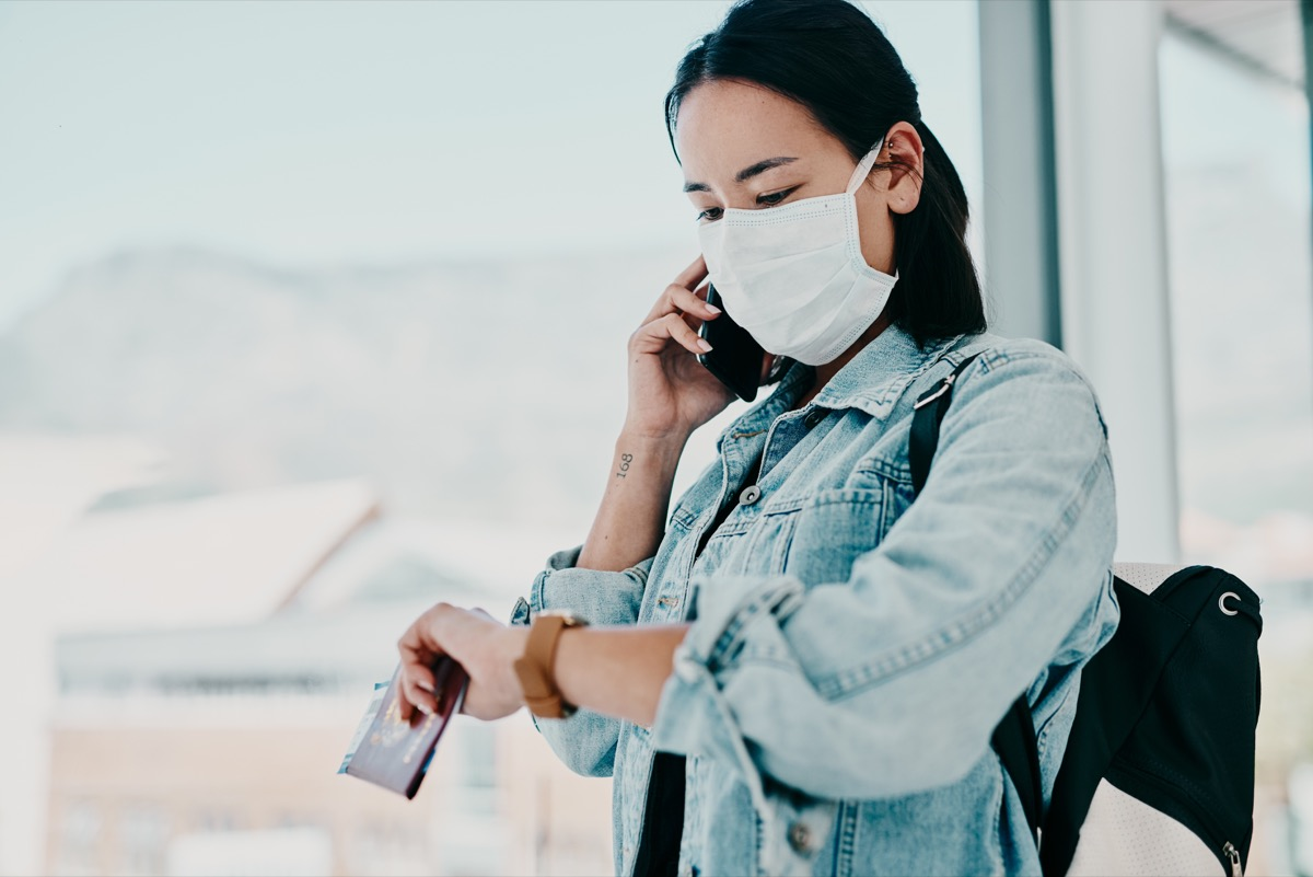 Shot of a young woman wearing a mask, using a smartphone and checking the time in an airport