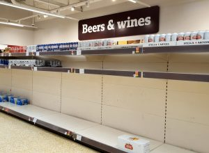 Shelves nearly empty of beer at a supermarket in as shoppers purchase supplies amid the coronavirus pandemic.