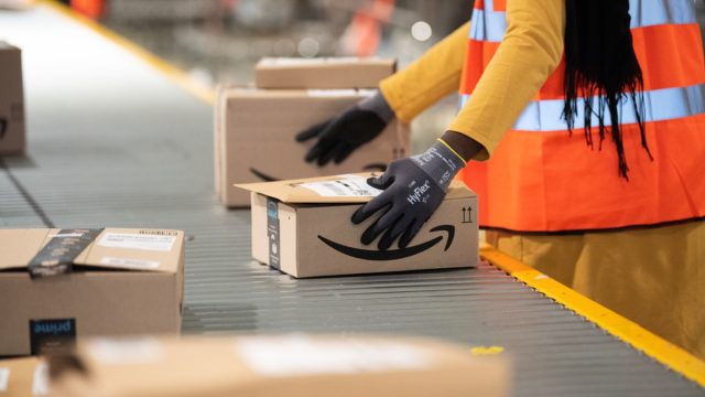 Amazon worker handling package in warehouse
