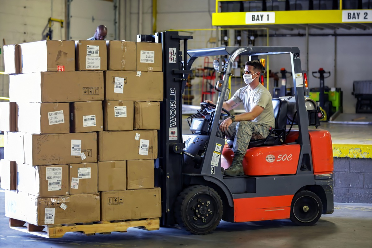 Forklift / lift truck driver operating forklift / lift truck and transporting goods / cargo / logistic from at Amazon warehouse or ship dock yard in crona virus in Berlin, Germany on 6th June 2020
