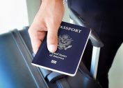 Close-up of someone holding an American passport over their suitcase