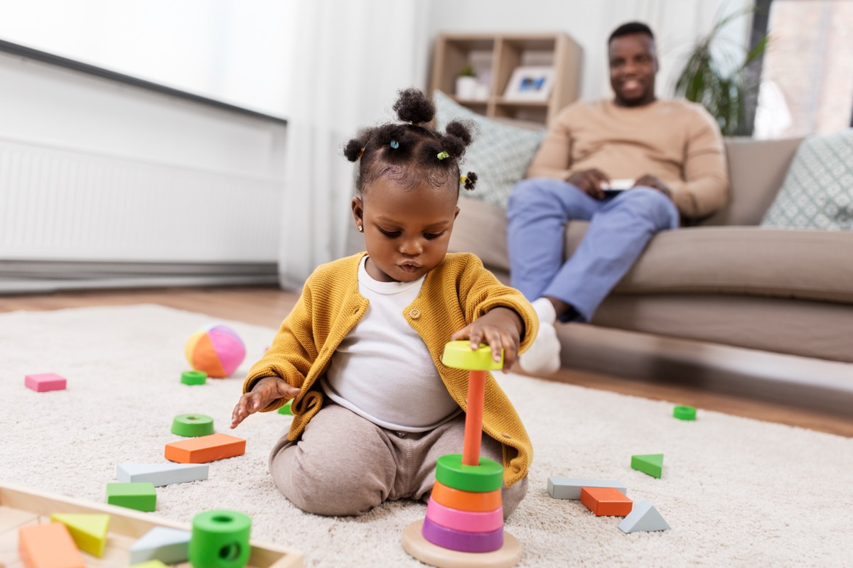 young child playing with blocks while her father looks on in background