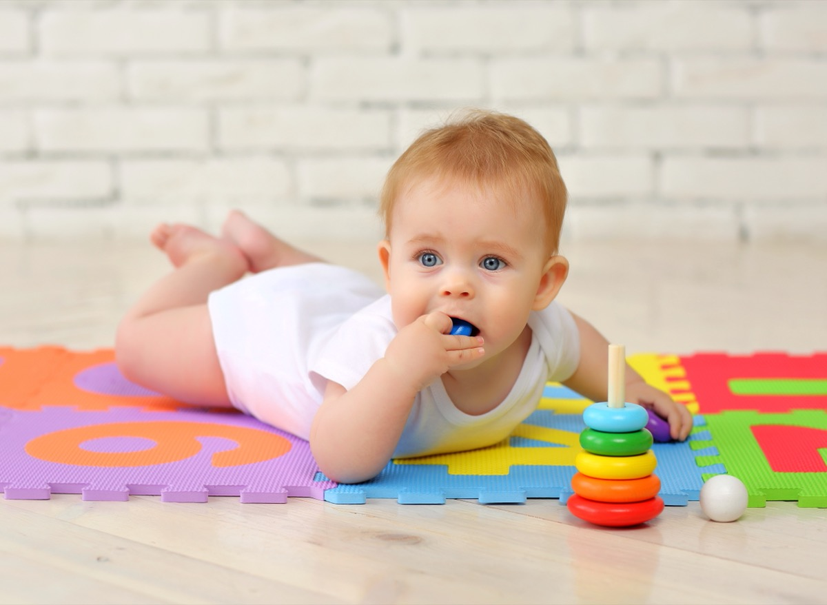 baby putting toy in mouth