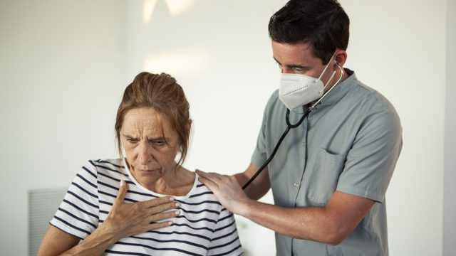 Doctor examining mature woman with stethoscope in living room during COVID - 19 pandemic