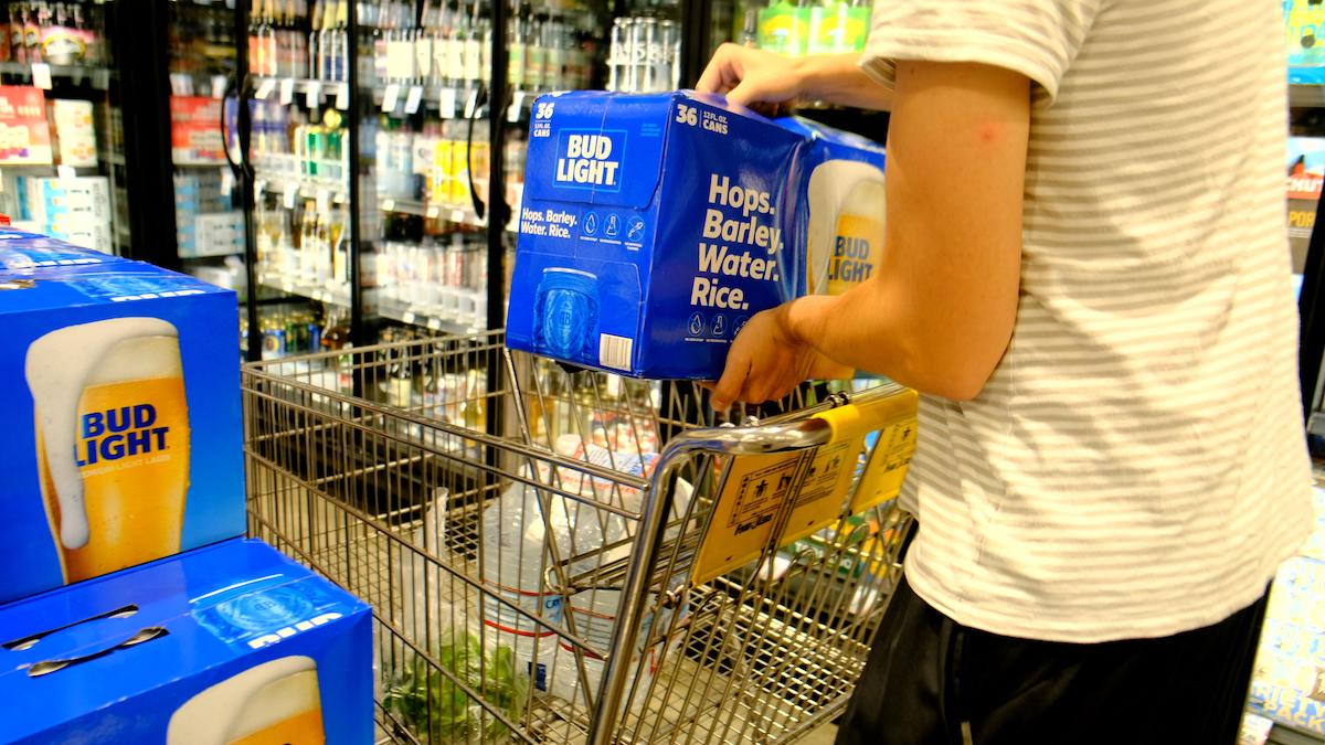 Shopper grabbing a case of Bud Light brand beer