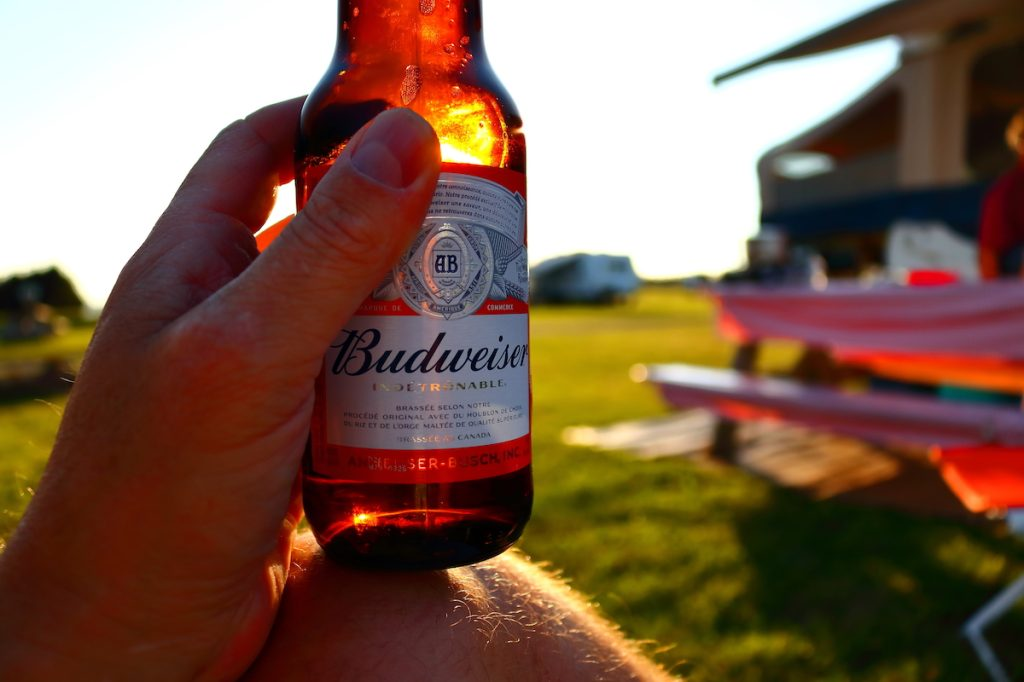 A person sitting at a campsite enjoying a Budweiser beer as the sun sets and the light highlights the bottle.