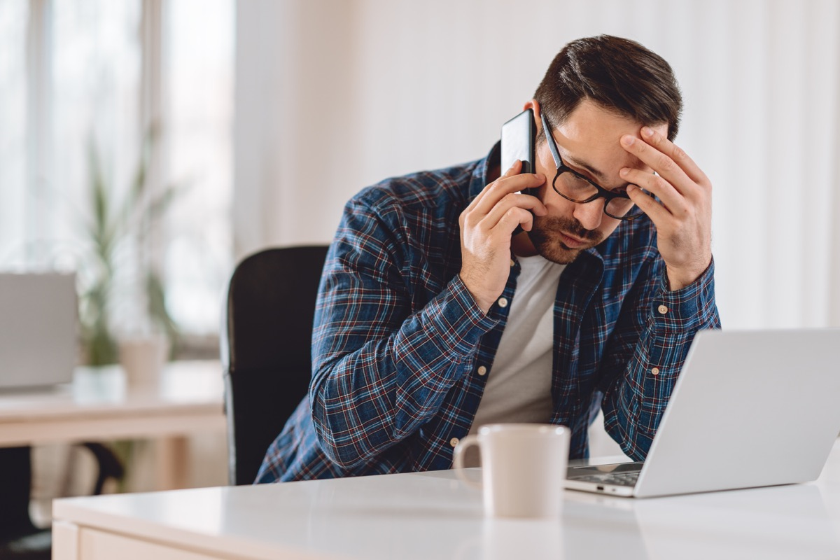 Worried businessman talking on phone in the office