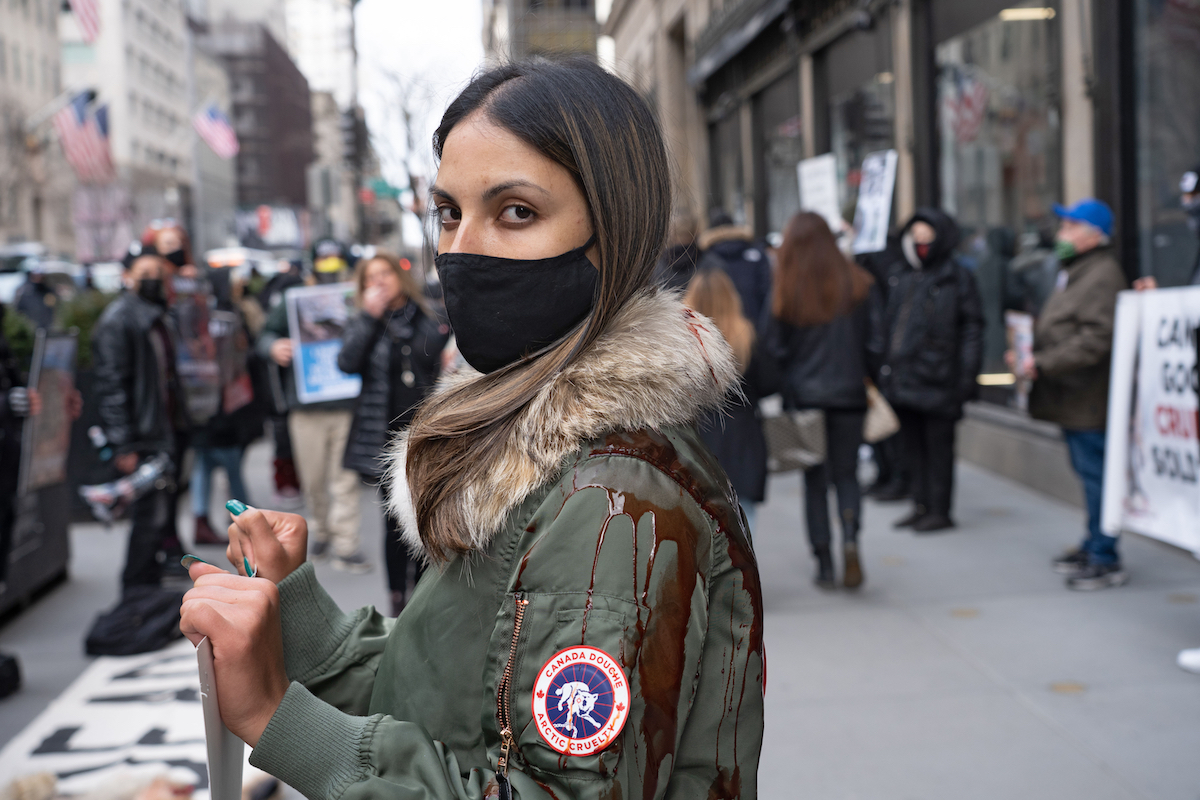A protester wearing Canada Goose coat cover with blood stands in a pool of blood during a Canada Goose protest in front of Saks Fifth Avenue flagship Store.