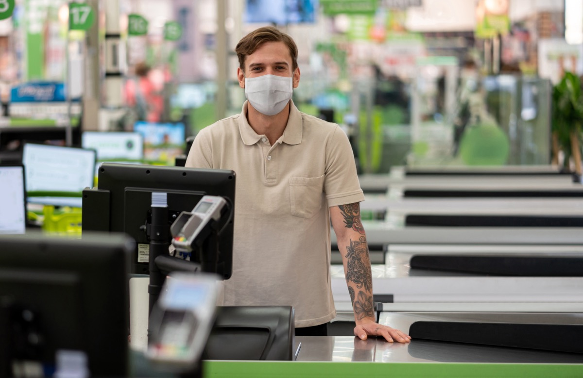 cashier working at a supermarket wearing a facemask during the COVID-19 pandemic