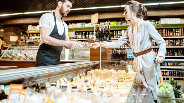 A young woman purchasing cheese from a monger at a cheese counter