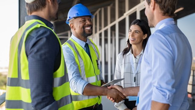 Smiling engineer shaking hands at construction site with happy architect.