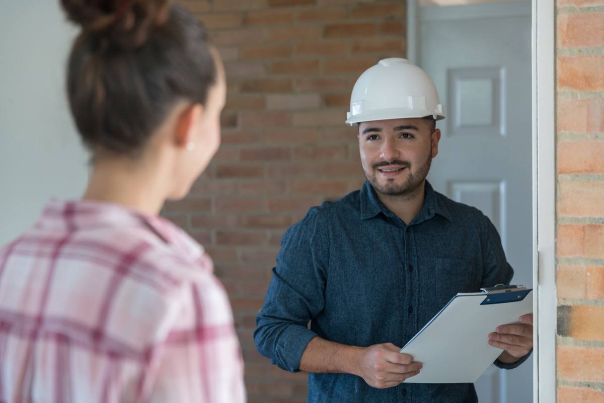 woman greeting a contractor at the door – home addition concepts